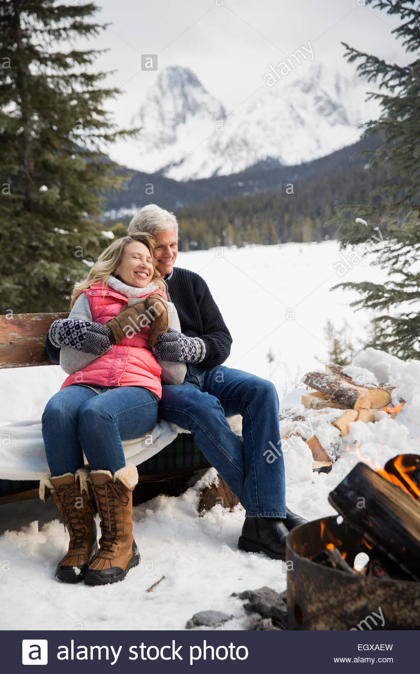 Couple relaxing at fire pit in snow - Stock Image