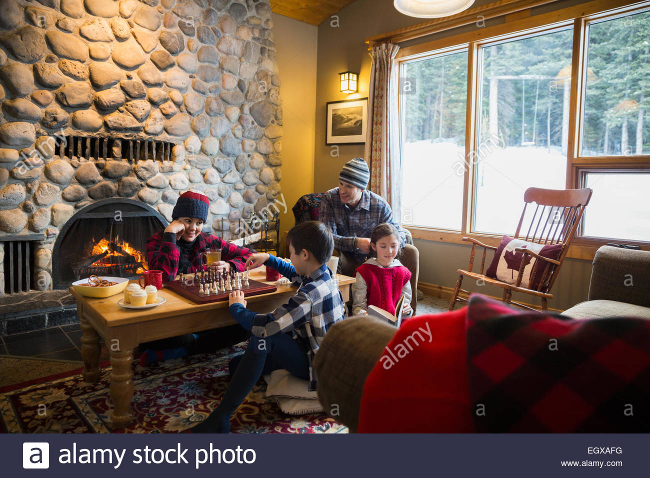 Family playing chess in lodge living room - Stock Image