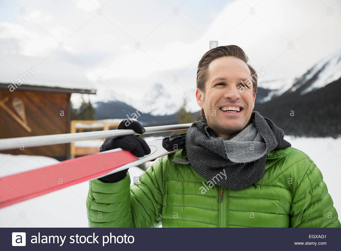 Smiling man with cross-country skis in snow - Stock Image