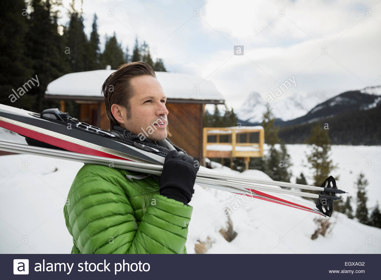 Pensive man holding cross-country skis in snow - Stock Image