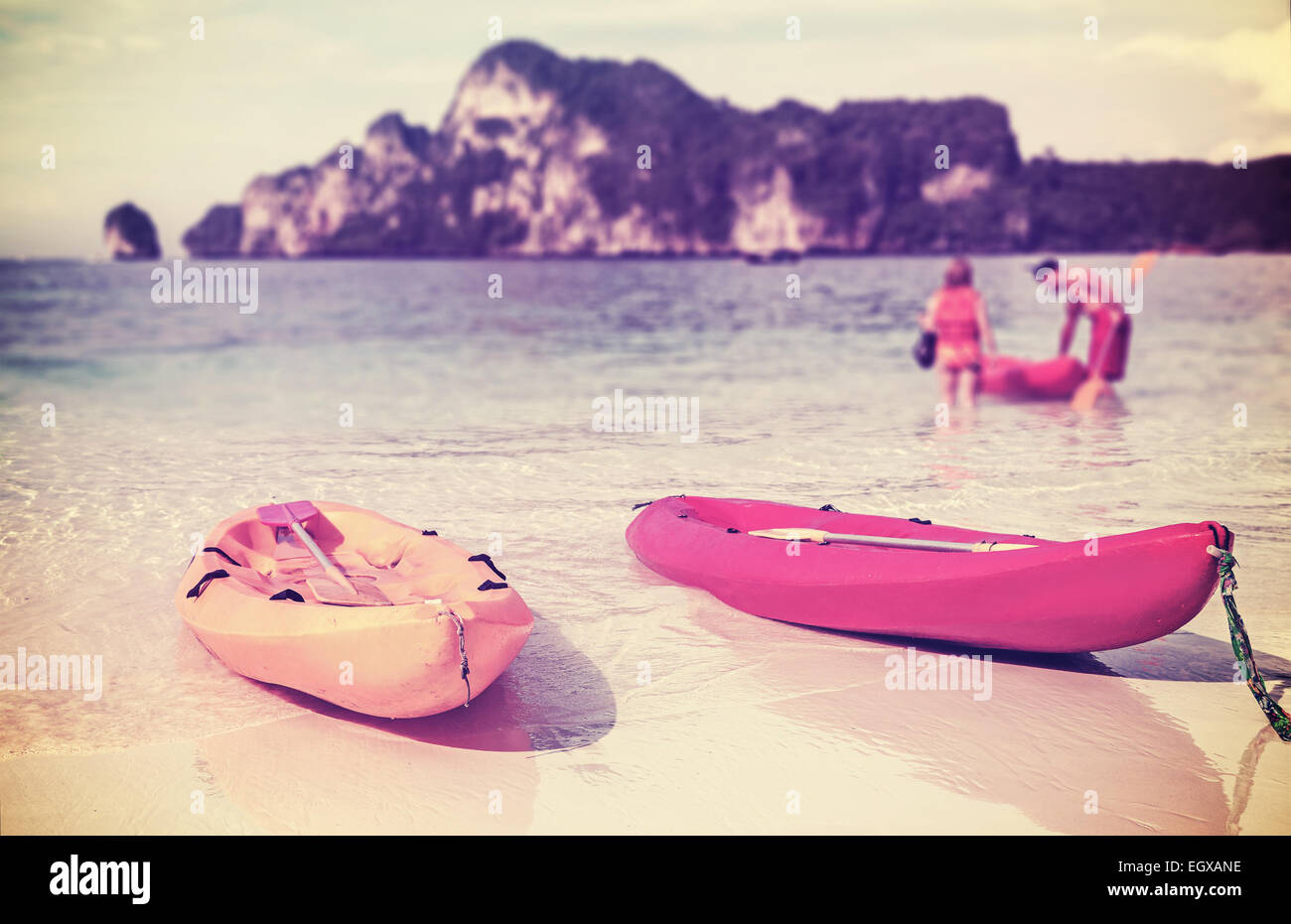 Retro filtered kayaks on a tropical beach, shallow depth of field. Active holidays background. - Stock Image