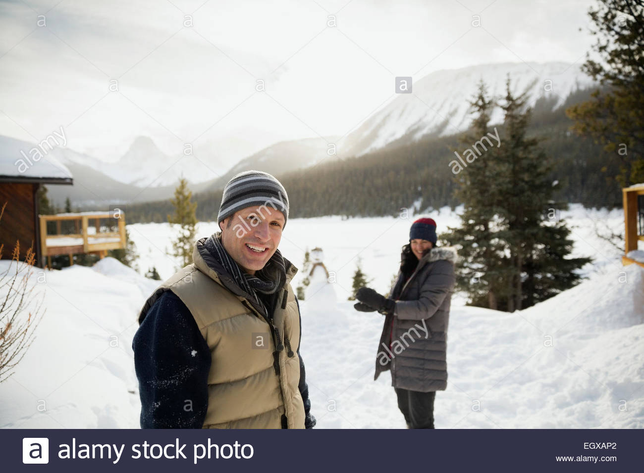 Portrait of smiling couple in snow below mountains - Stock Image
