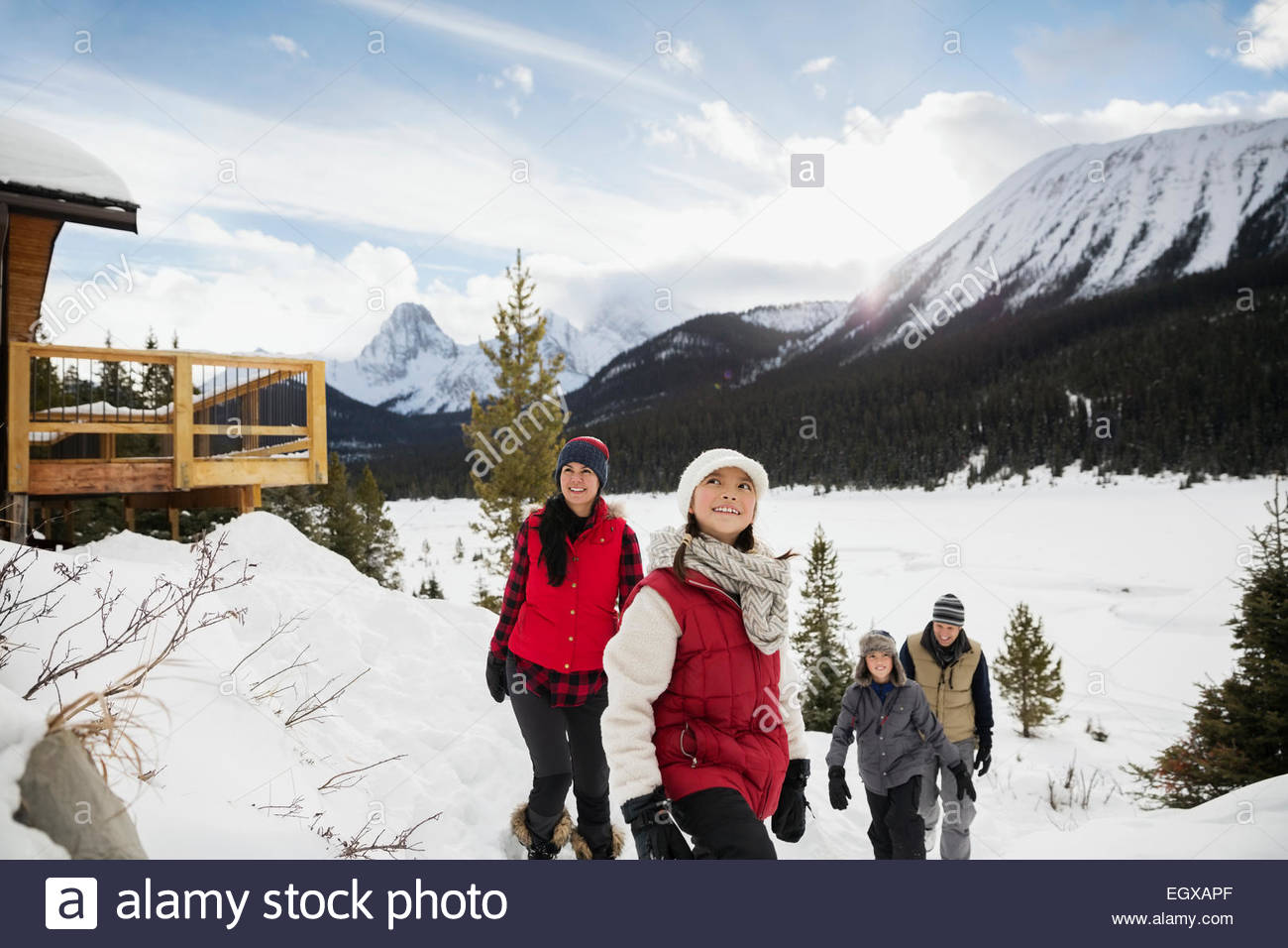 Family in snow below mountains - Stock Image