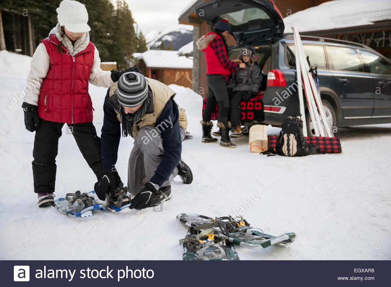 Father fastening snowshoes on daughter in snowy driveway - Stock Image