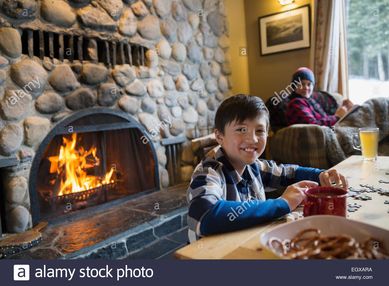 Boy assembling jigsaw puzzle by living room fireplace - Stock Image