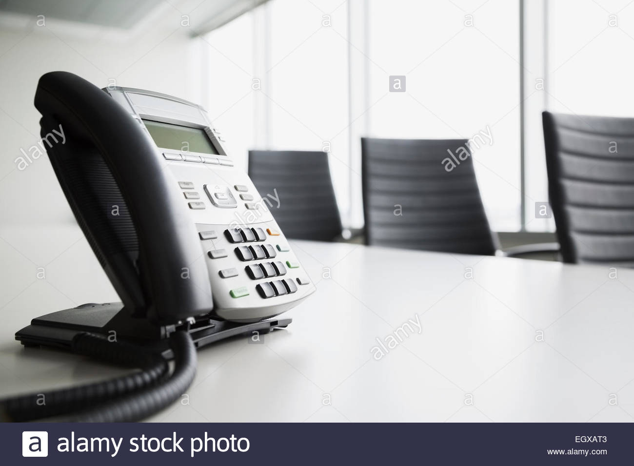 Conference telephone on empty conference room table - Stock Image