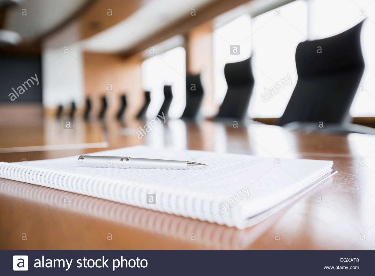 Notepad and pen on empty conference room table - Stock Image