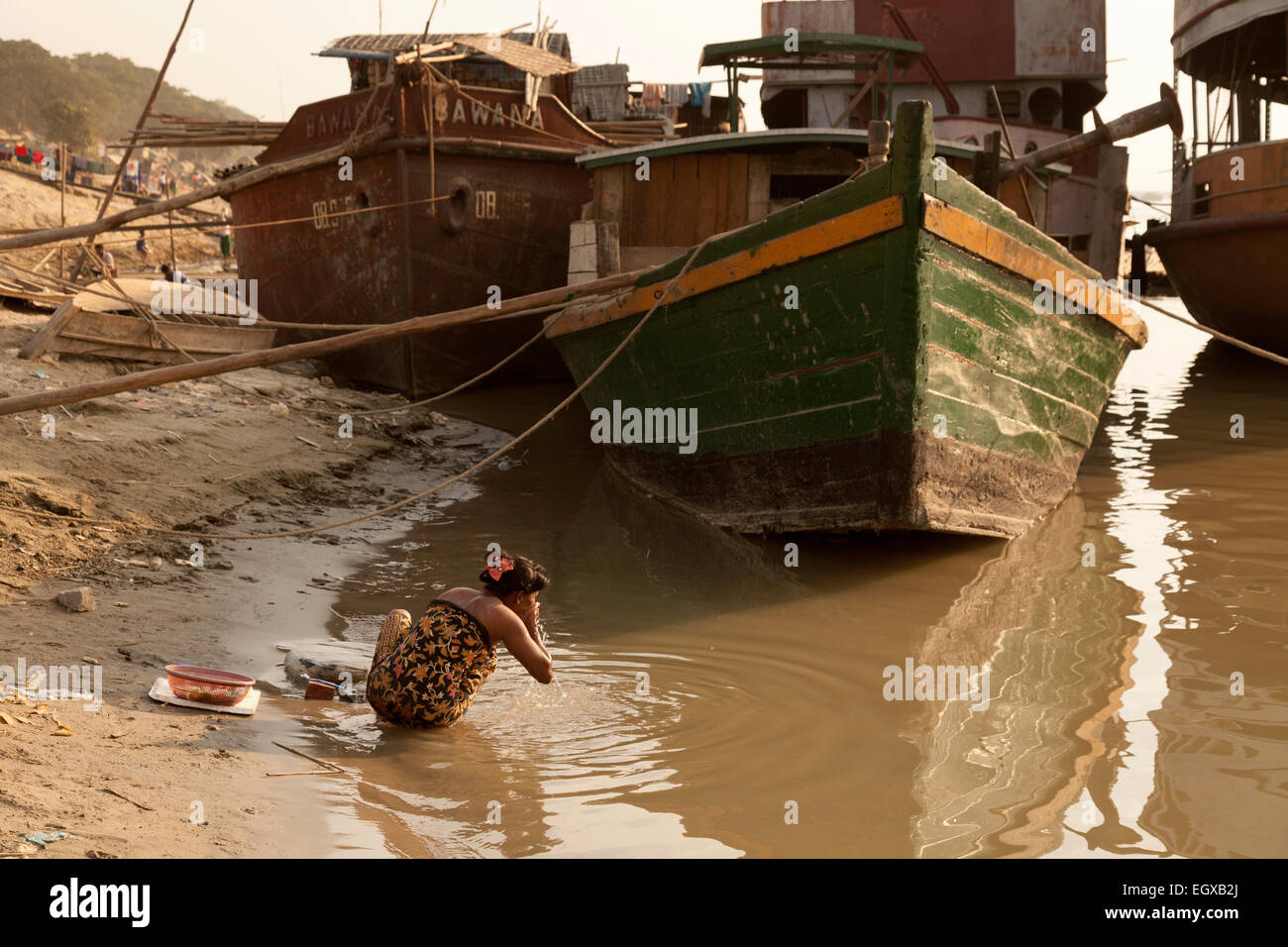 A young burmese woman washing her face in the polluted waters of the Irrawaddy River at Mandalay, Myanmar ( Burma - Stock Image