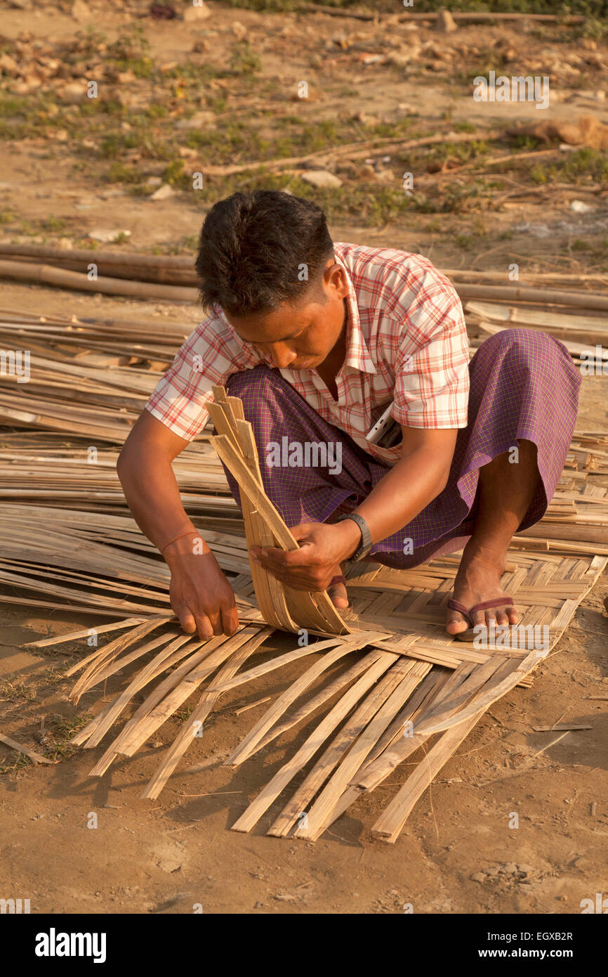 A craftsman weaving the roof of a hut out of wooden slats, Mandalay, Myanmar ( burma ), Asia - Stock Image