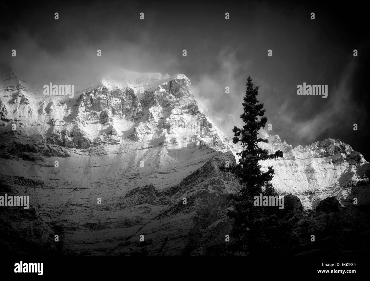 First light on mountain, surrounding Moraine lake with fresh snow. Banff National Park, Alberta, Canada - Stock Image