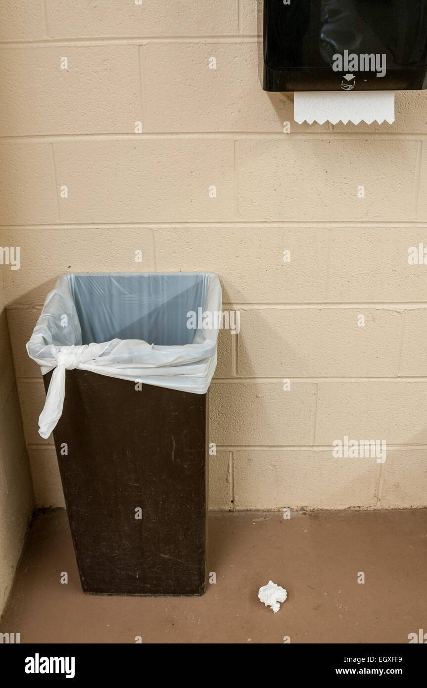 A restroom garbage can with a paper towel thrown on the floor next to it. - Stock Image