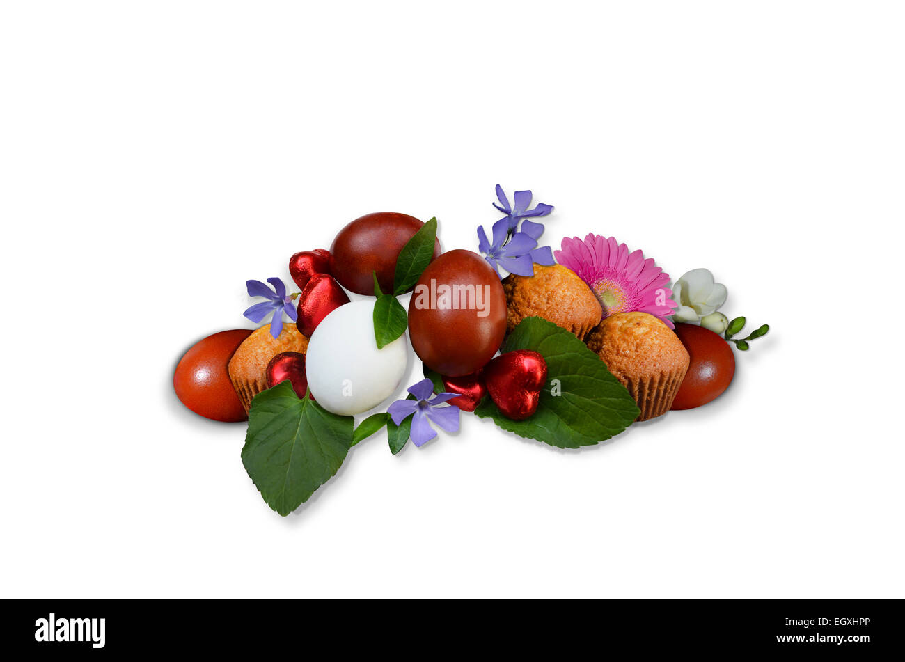 Easter eggs with pastries and flowers on a white background - Stock Image