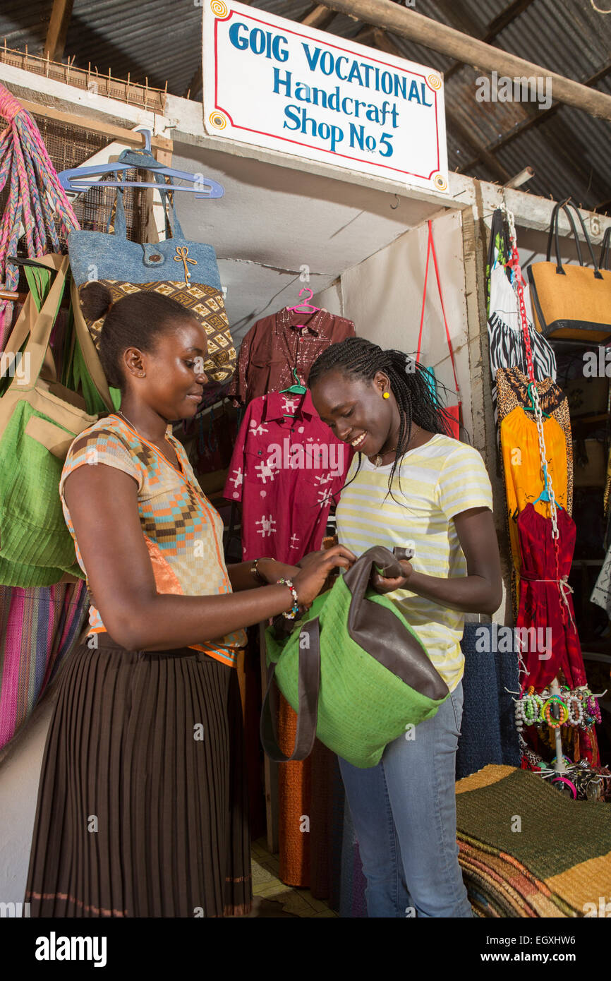 A customer shops for handmade bags in a handicraft workshop and retail store in Dar es Salaam, Tanazania, East Africa. - Stock Image