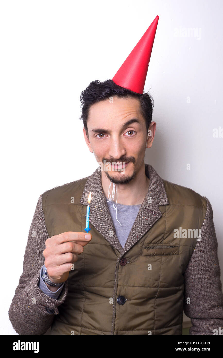man in his thirties holding a birthday candle and looking dubious. - Stock Image