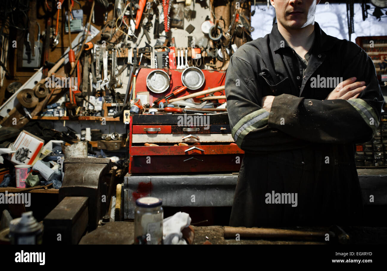 Arm Crossed Worker in a Shed and Lots of Tools Hanging on the Wall Stock Photo