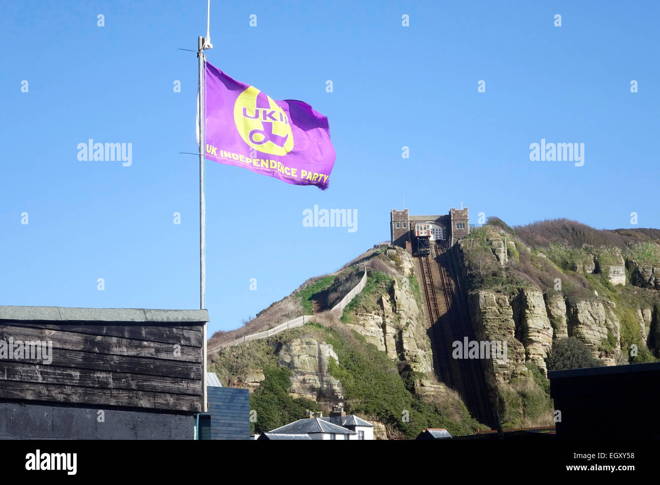 UKIP Flag flying over fishing huts on Hastings Stade  East Sussex England - Stock Image