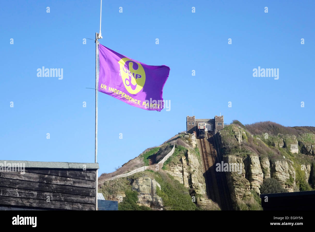 UKIP Flag flying over fishing huts on Hastings Stade beach East Sussex, GB - Stock Image
