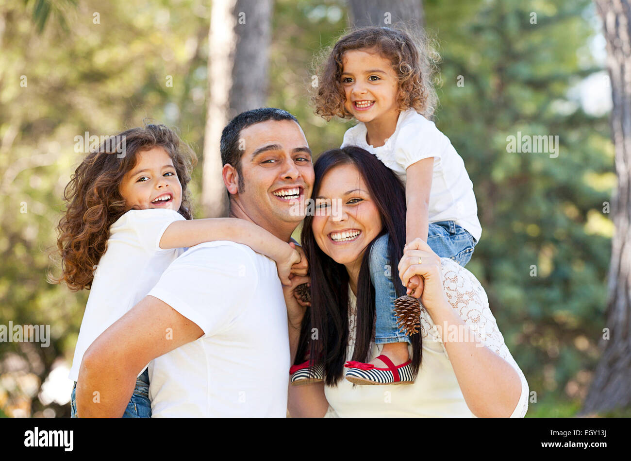 happy hispanic people parents giving children piggyback - Stock Image