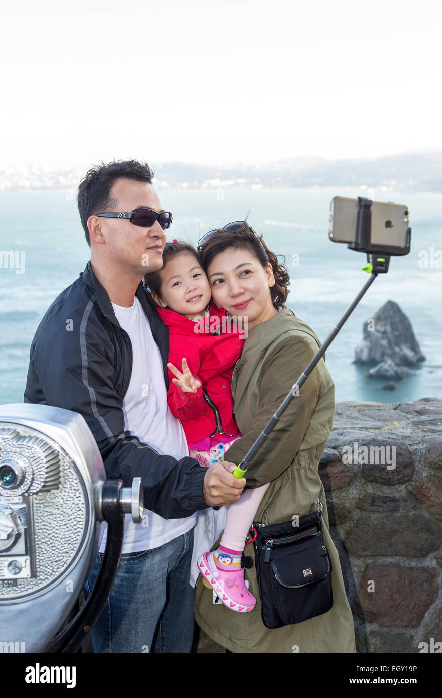 tourists, family, taking selfie, selfie photo, selfie stick, Vista Point, north side of Golden Gate Bridge, city - Stock Image