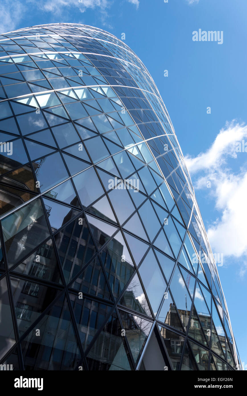 Reflections of other buildings in the London Gherkin against a mainly blue sky - Stock Image