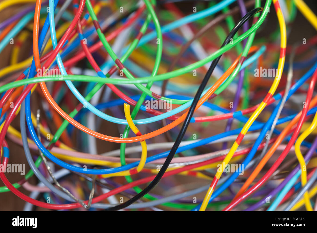 spaghetti junction mass of different colored network computer cables twisted and tangled to supply data - Stock Image