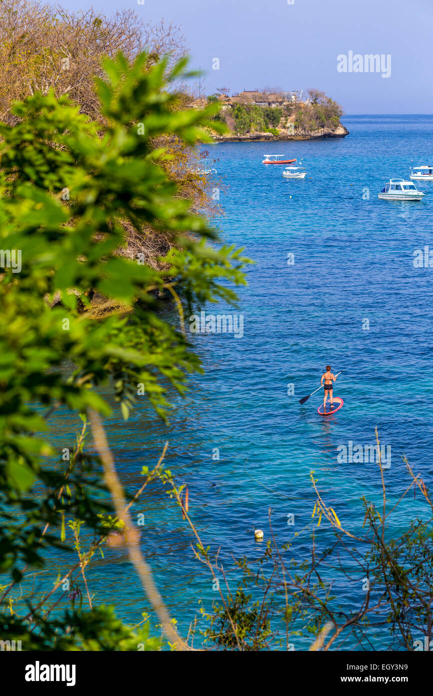 Woman travels by SUP at coastline of Nusa Lembongan and Nusa Ceningan islands, Indonesia. - Stock Image