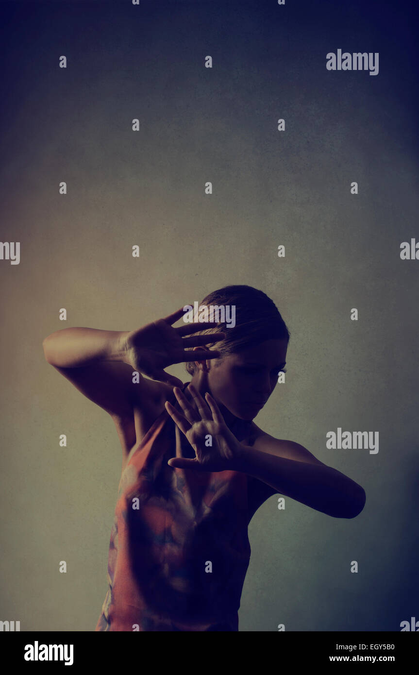 Scared young woman hiding face - Stock Image
