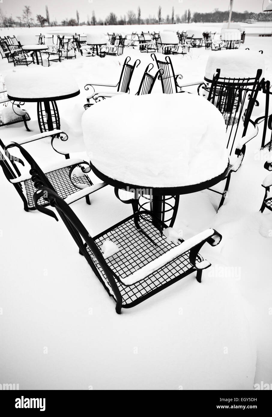 Chairs and table from a local coffee shop cowered with snow - Stock Image