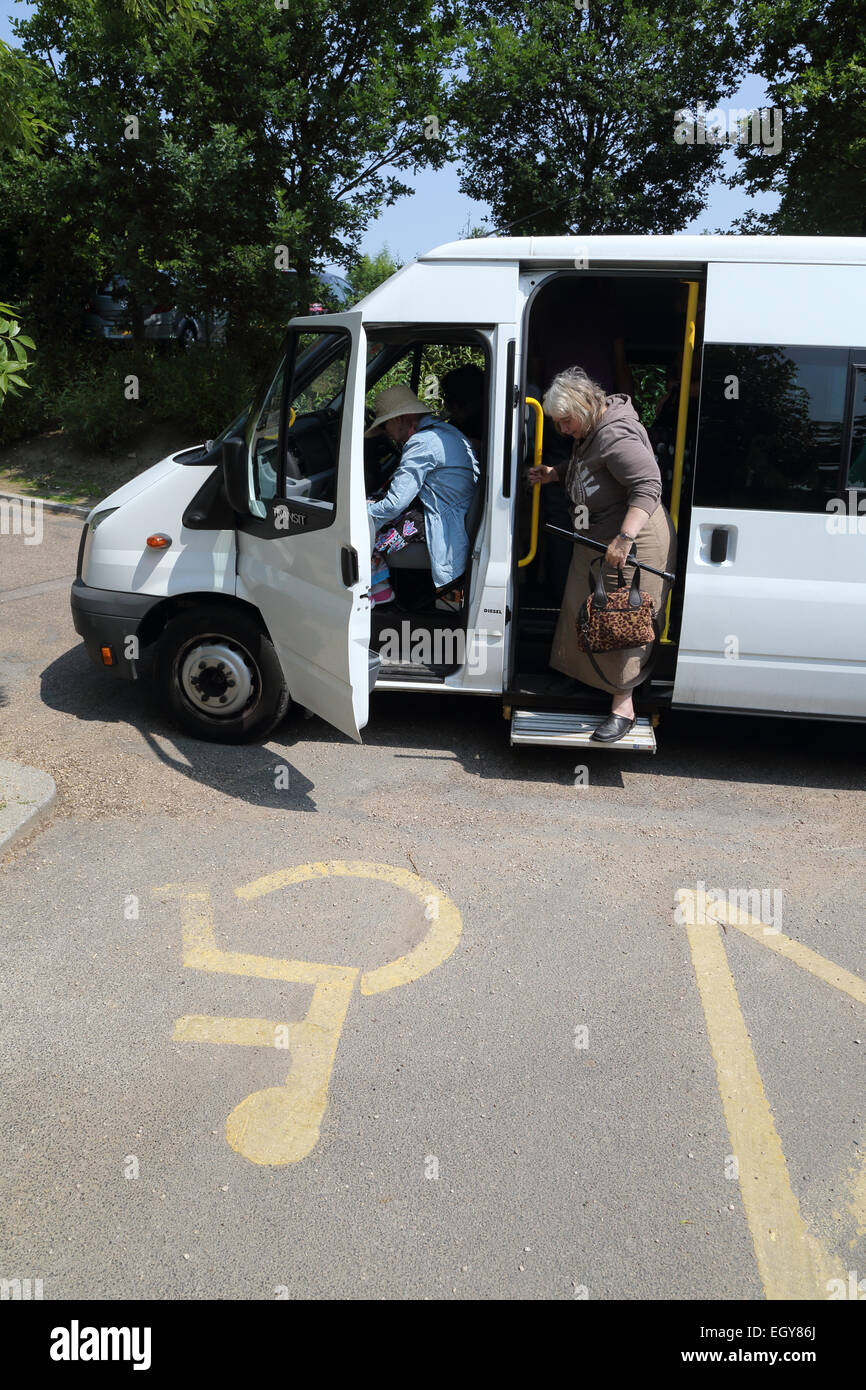 People getting off a minibus next to disabled parking bay. - Stock Image