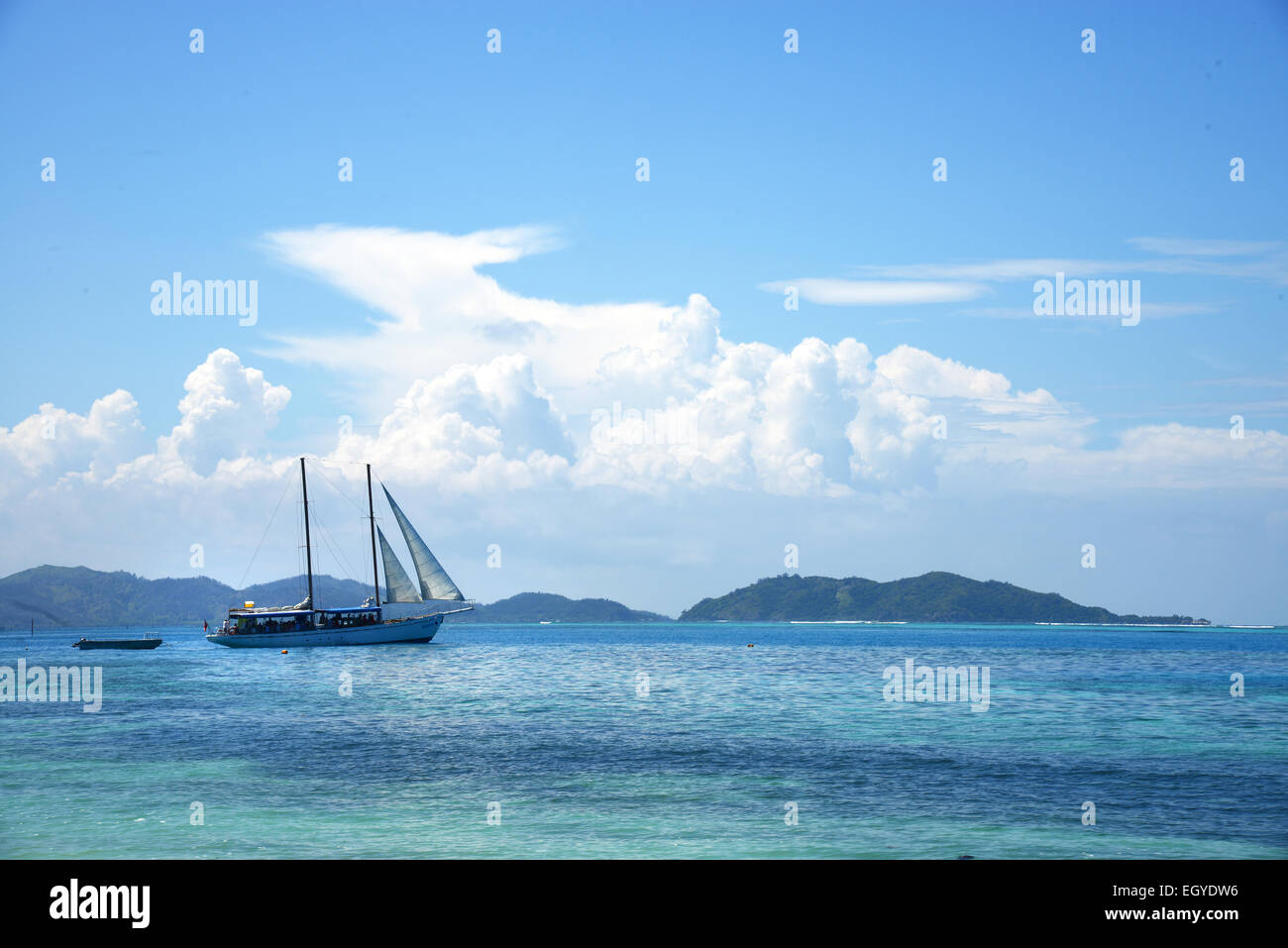 A sail boat cruises off the island of Malolo, Fiji. - Stock Image