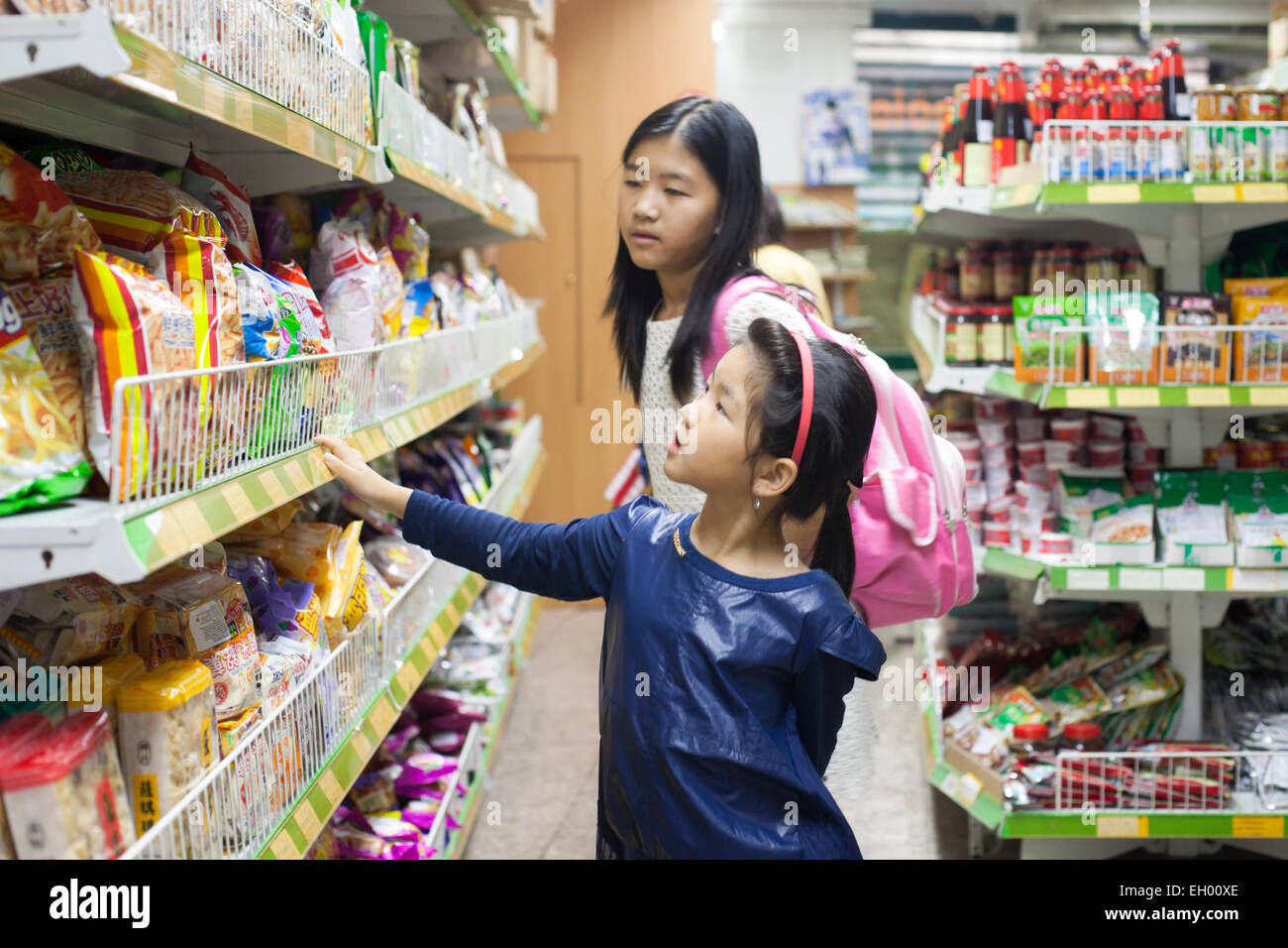 Girl at small Chinese supermarket in Lisbon. Wealthy Chinese property buyers are attracted to Portugal by its golden - Stock Image