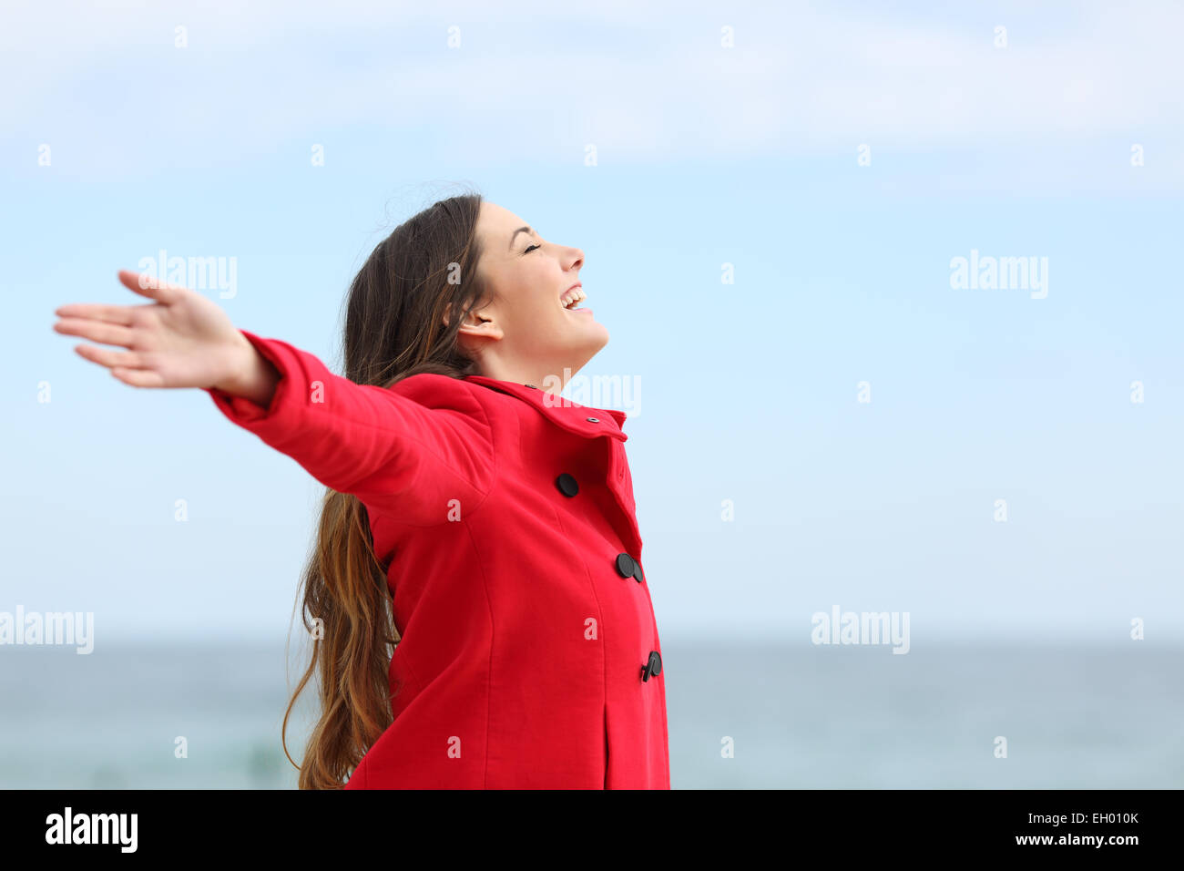 Happy fashion woman profile breathing deep fresh air in winter on the beach - Stock Image