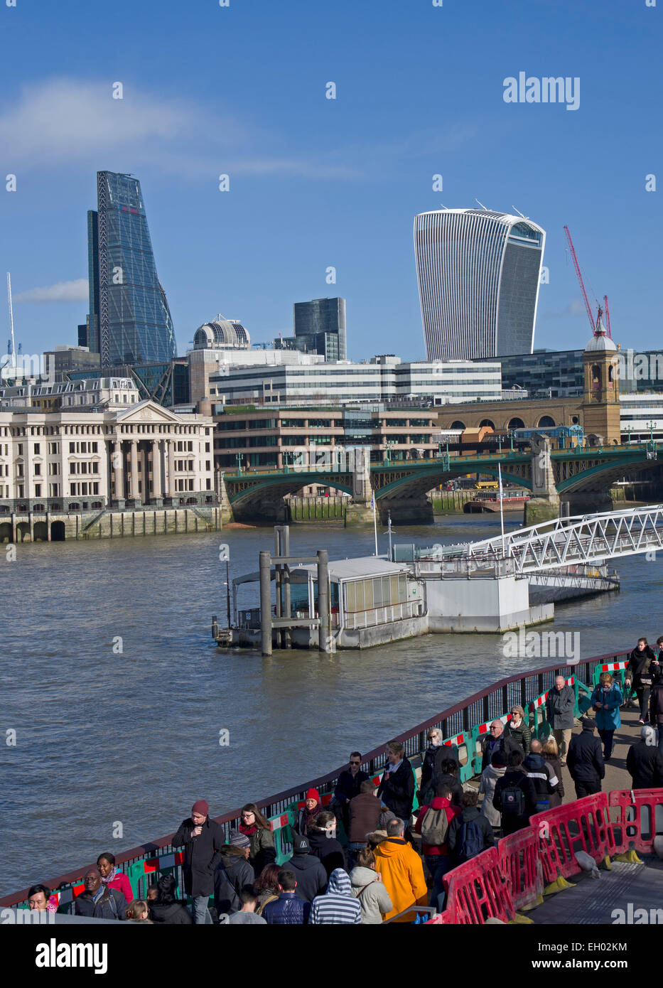 Visitors crowd the paths of the South Bank. View of the latest buildings of The City of London from the Millennium - Stock Image