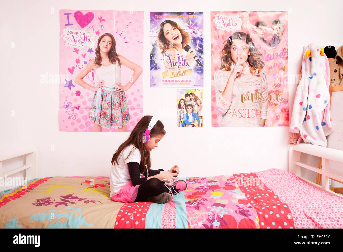 Violetta child fan listening to the TV series music on her bedroom   covered with Violetta posters. - Stock Image