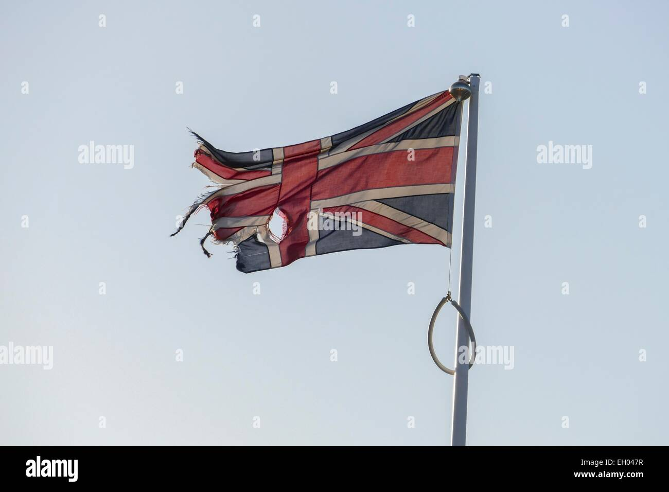 A ripped Union Jack flying from a flagpole - Stock Image