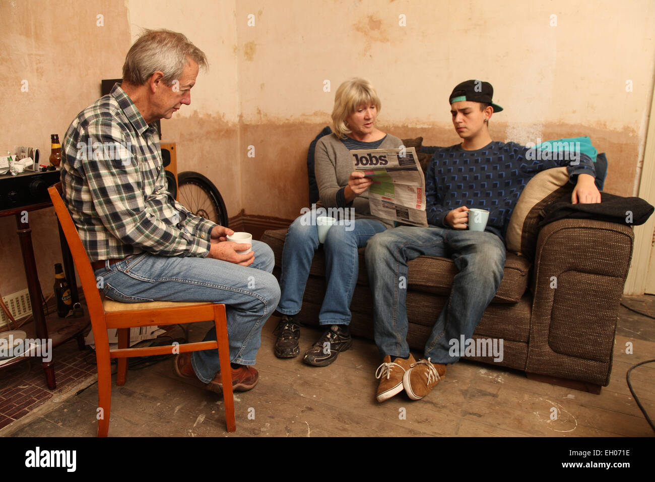Teenager with grandparents looking at newspaper for jobs - model released - Stock Image