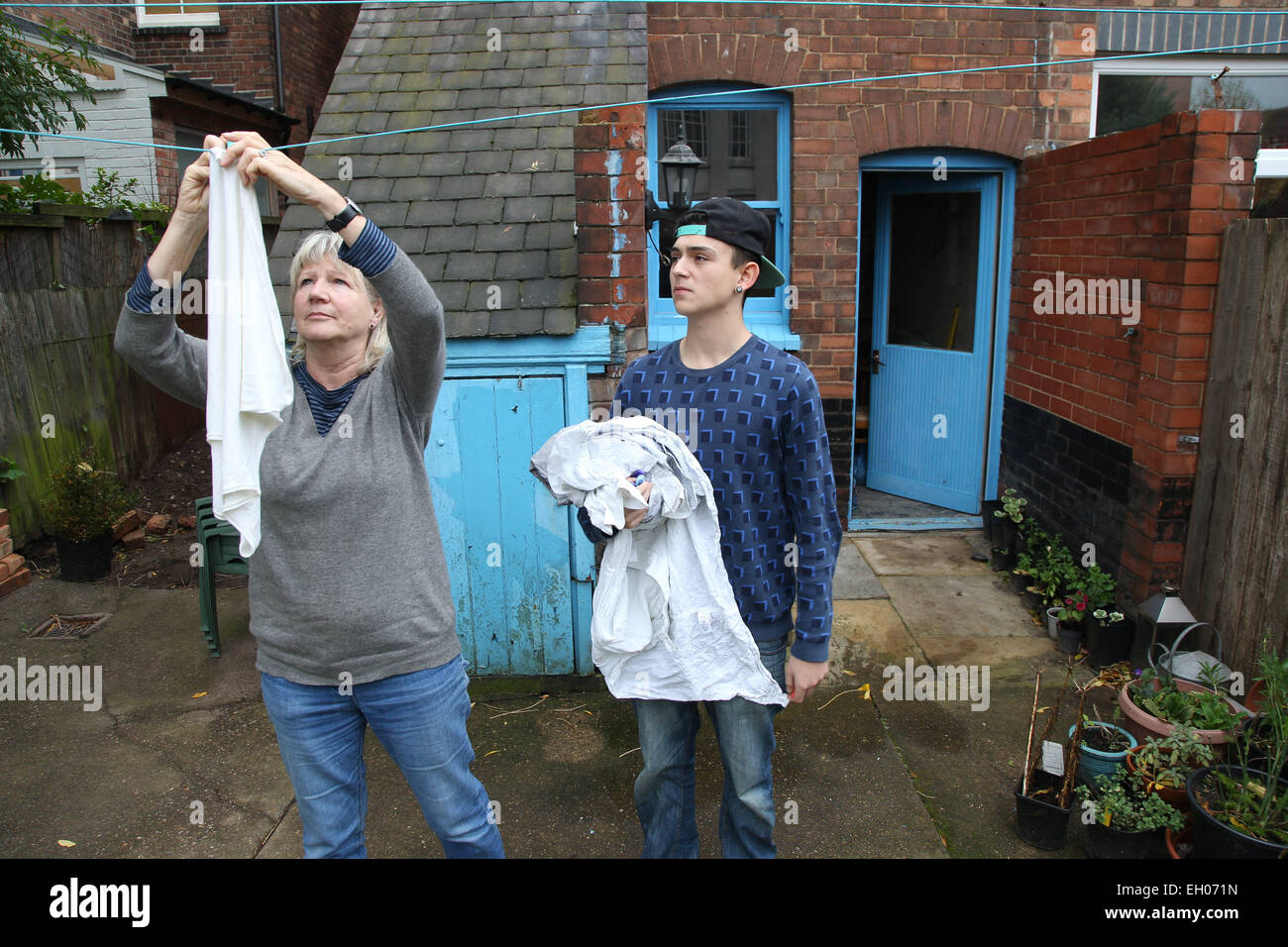 Teenager helping grandmother with hanging washing - model released - Stock Image