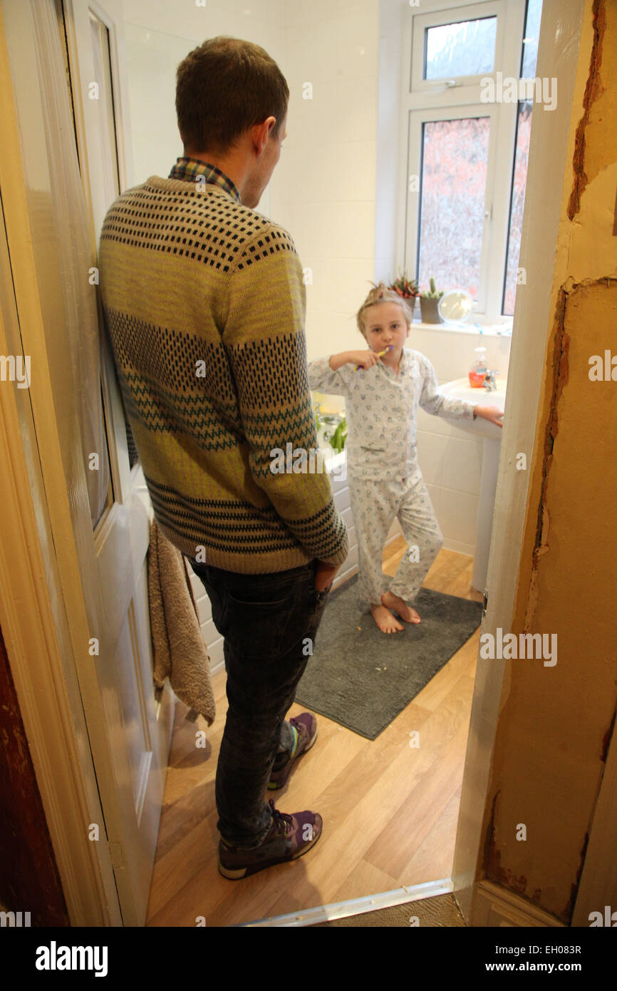 Father watching daughter brushing teeth - model released - Stock Image