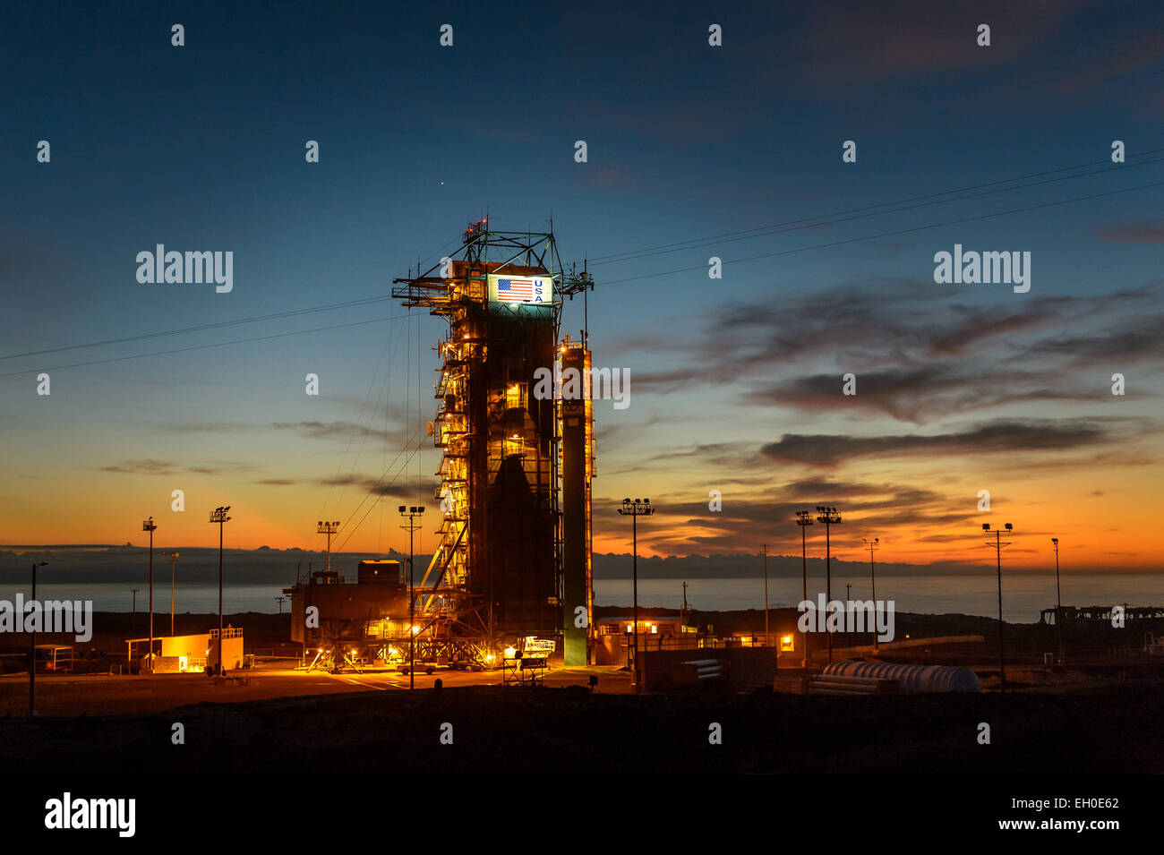 The sun sets behind Space Launch Complex 2 (SLC-2) with the Delta II rocket and the Soil Moisture Active Passive - Stock Image