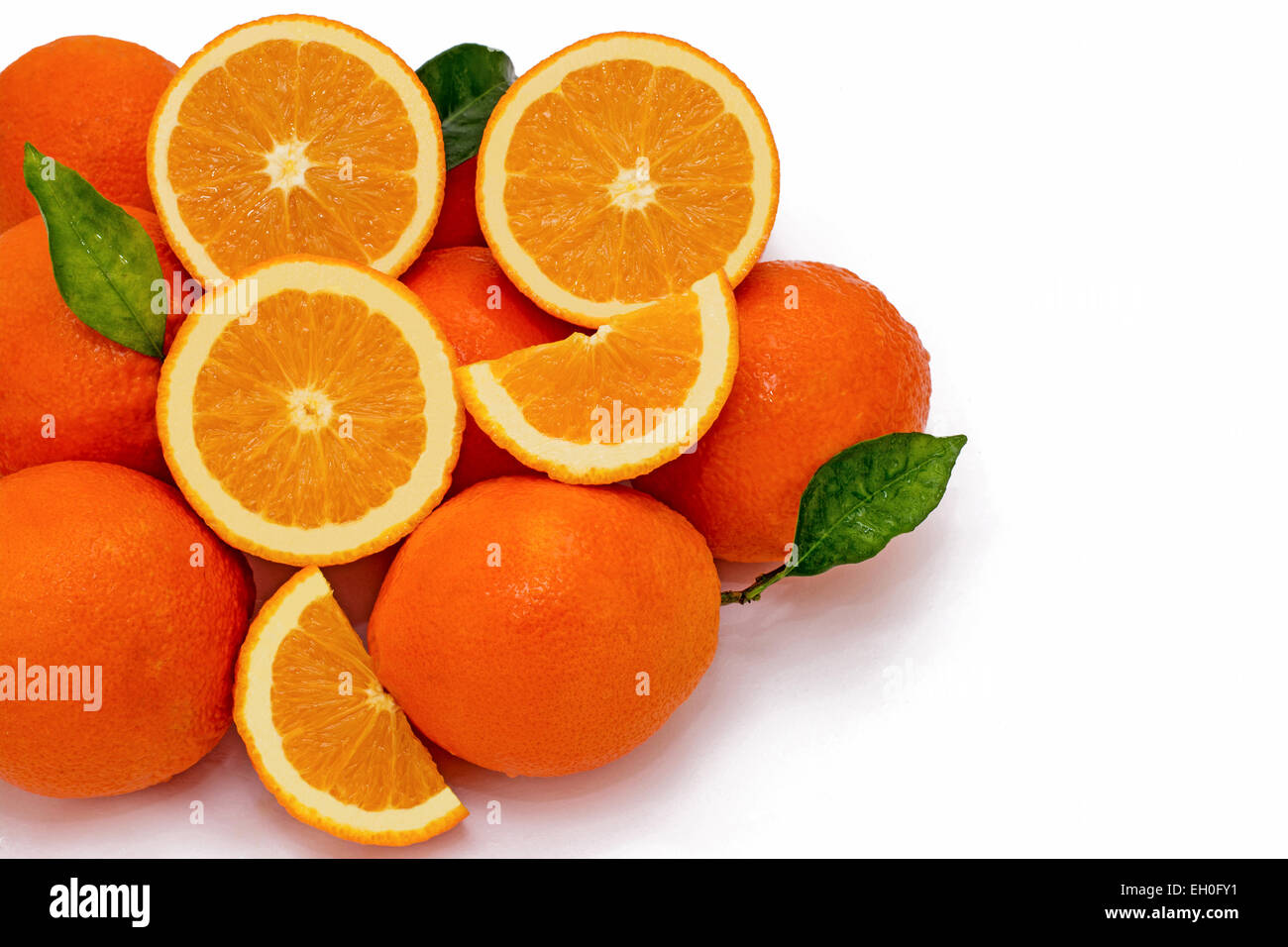 A group of Juicy Oranges half quarter  whole with green leaves on a white background and room for text - Stock Image