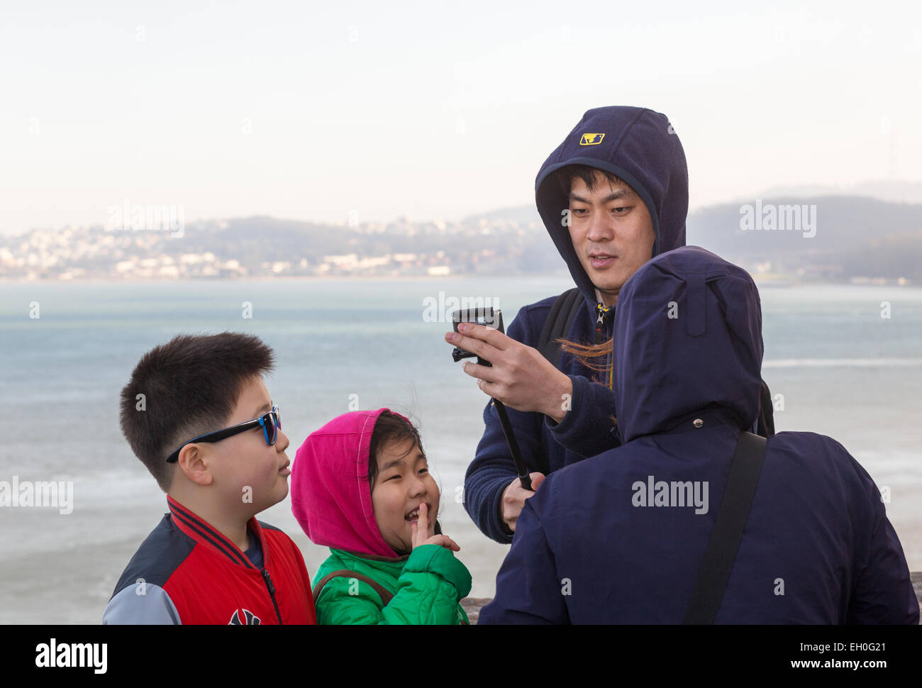 Asian man, using selfie stick, taking selfie photo, Vista Point, north side of Golden Gate Bridge, city of Sausalito, Stock Photo