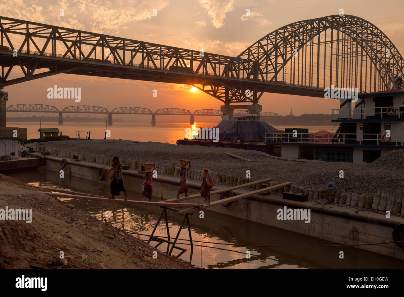 Sunset over the railway bridges over the Irrawaddy river at Mandalay, women working in the foreground,  Myanmar - Stock Image