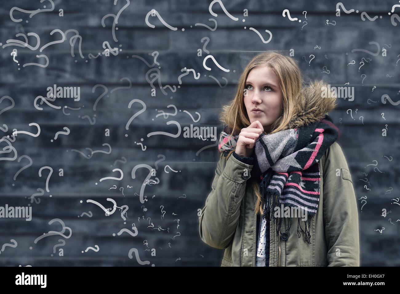 Pretty young female student in class with a problem to solve standing in front of a chalkboard in class covered - Stock Image