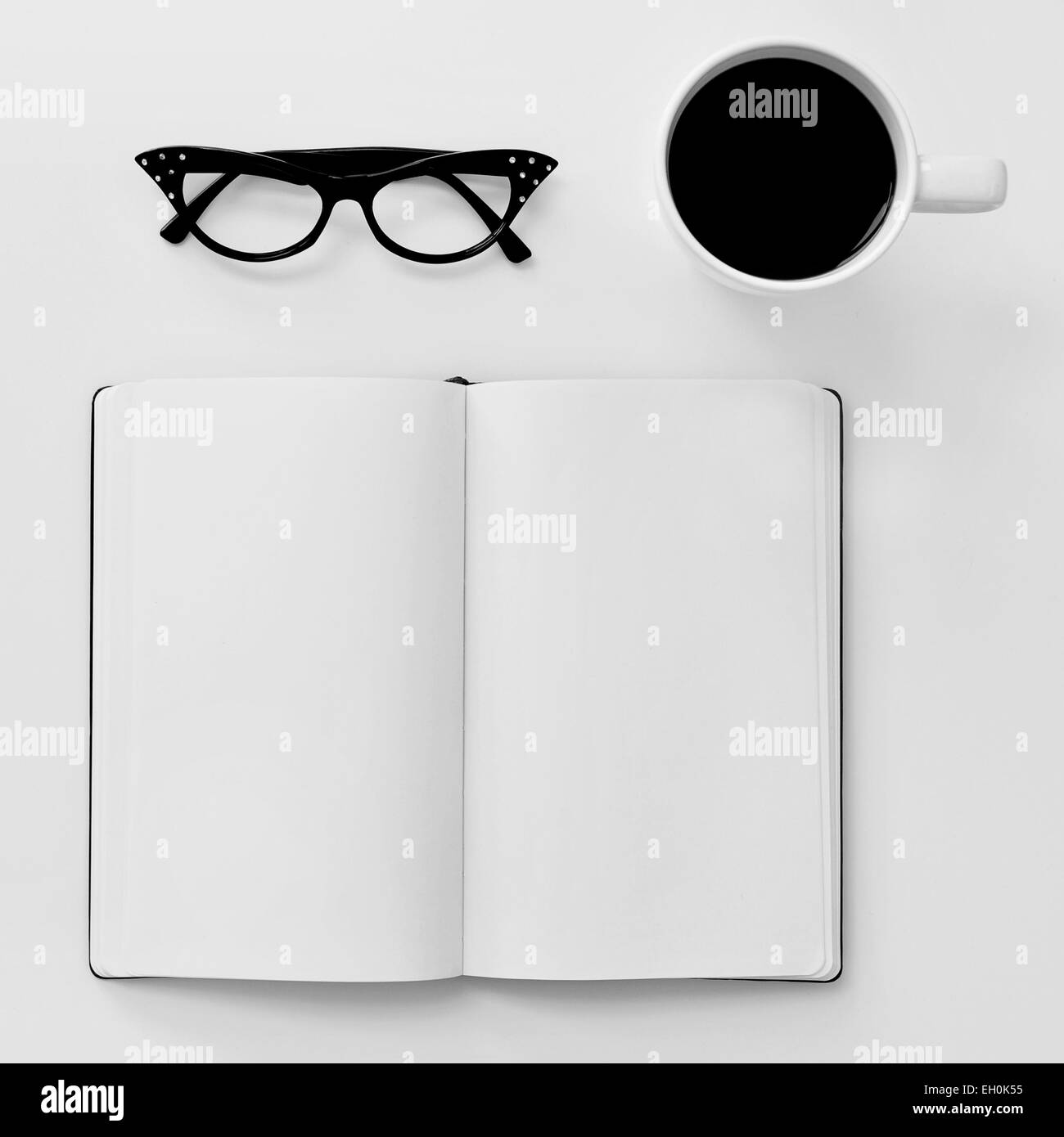 high-angle shot of a blank notebook, a pair of black plastic-rimmed eyeglasses for women and a cup of coffee on - Stock Image