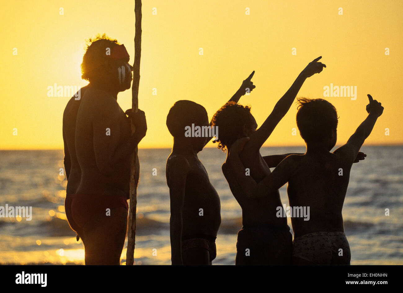 Aboriginal with a pole and children pointing at the sky at sunset, Darwin, Australia - Stock Image