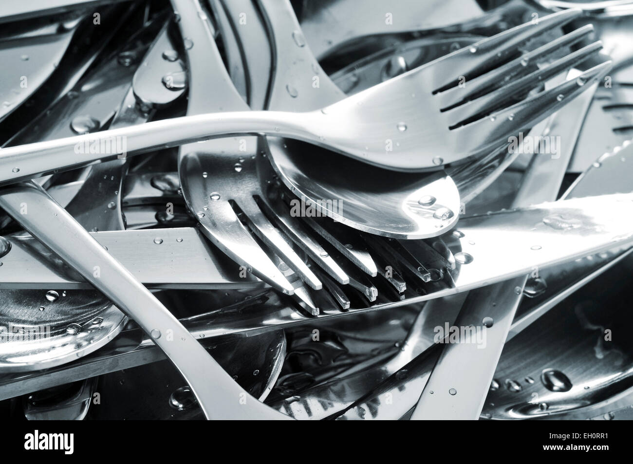 closeup of a pile of wet knifes, forks and spoons - Stock Image