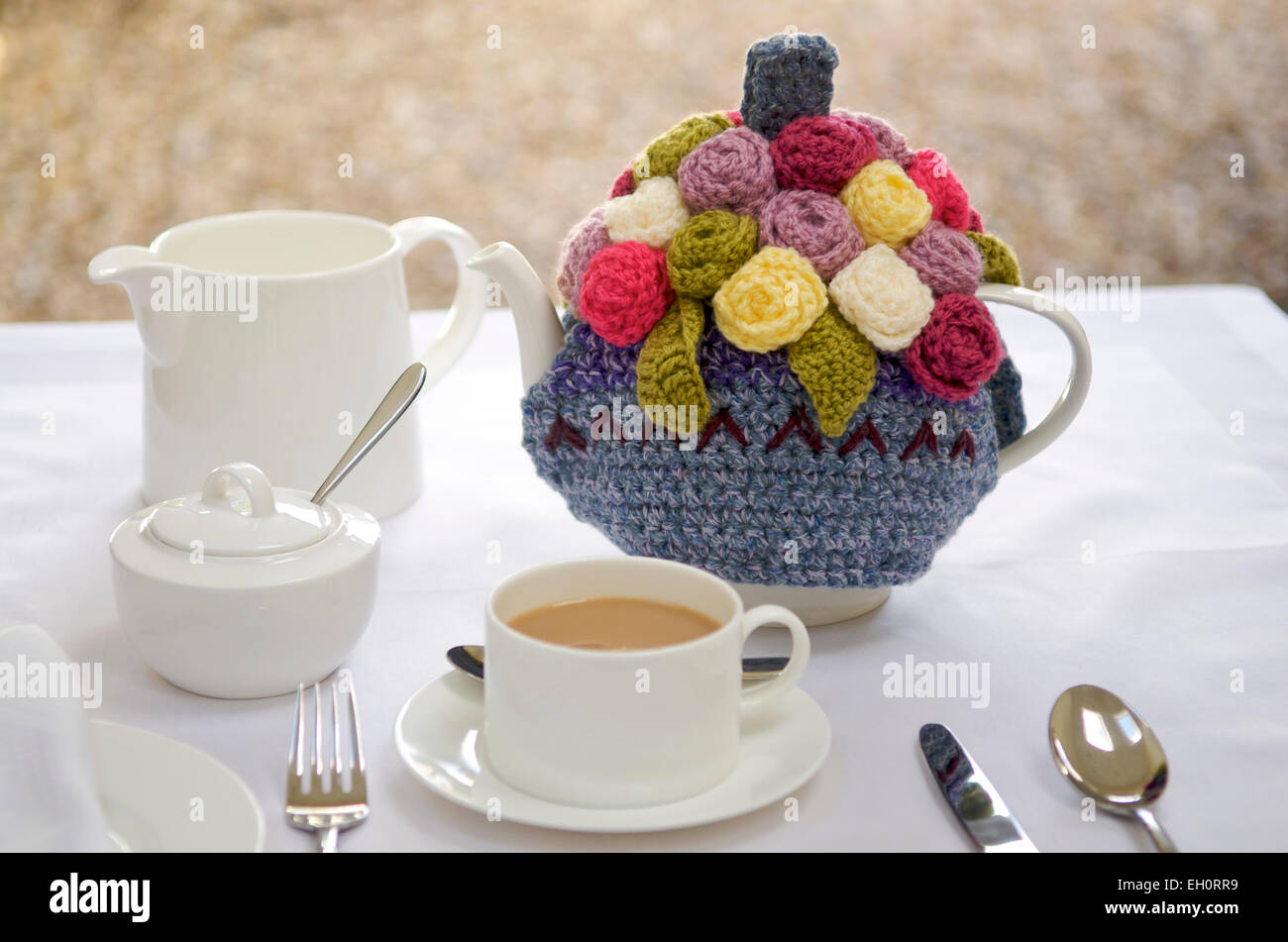 Ornate tea cosy on a teapot - Stock Image