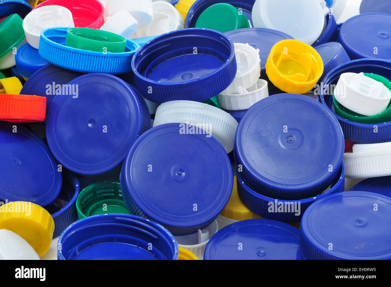 closeup of a pile of plastic screw caps of different colors and sizes - Stock Image