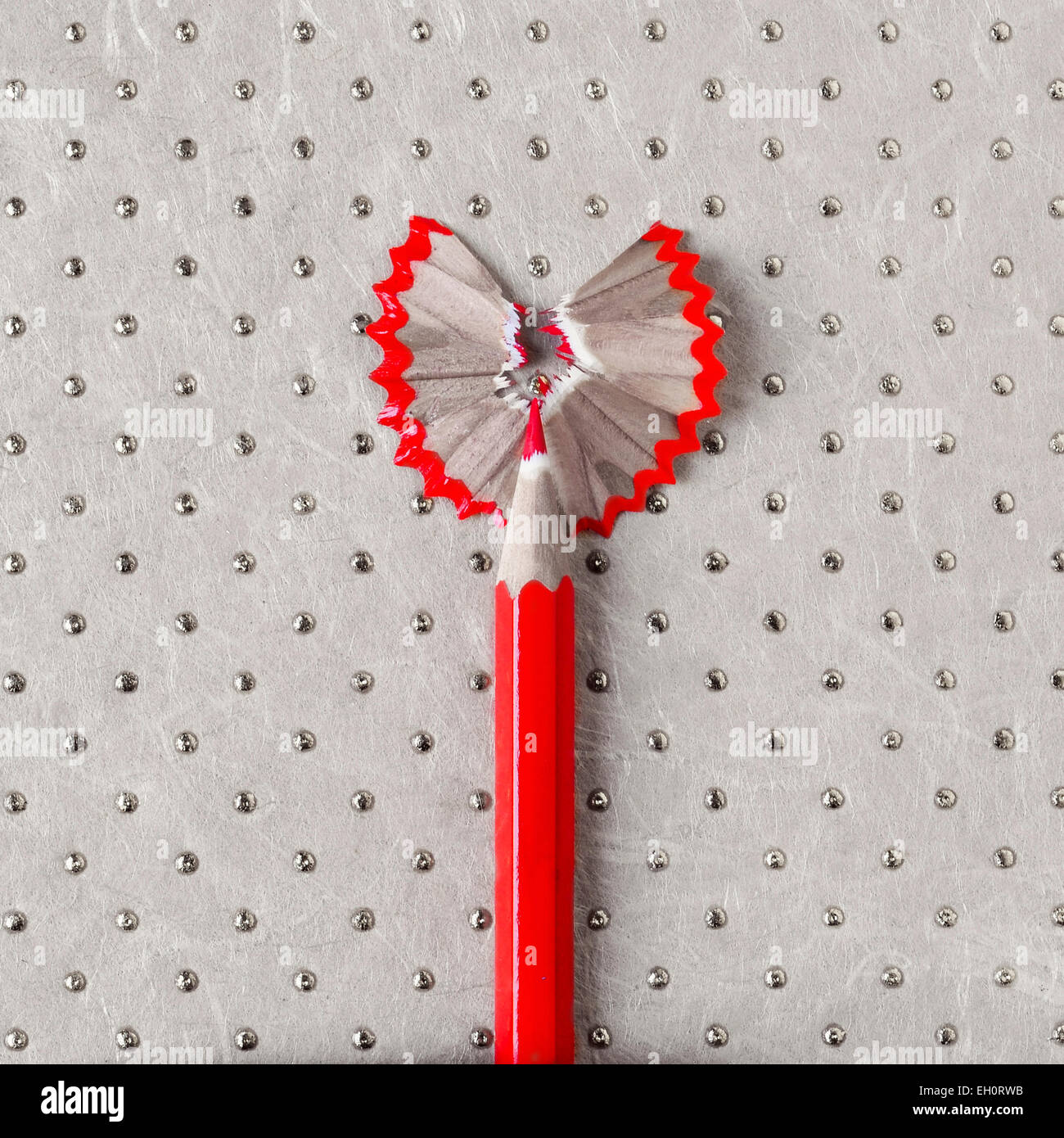 a sharpened wooden red coloured pencil with its shavings forming a heart on a patterned background - Stock Image