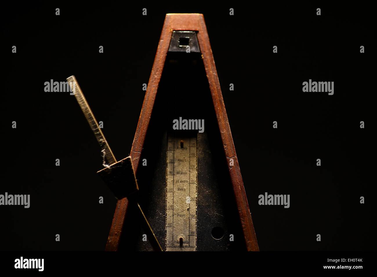 Horizontal shot of a vintage metronome, on a black background. - Stock Image